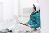 the girl wearing spectacles in casual clothes of mint color works with a laptop on the Internet - 184735670