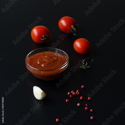Fotobehang Kersen Juicy ripe tomatoe and and tomato sauce or ketchup in glass bowl.