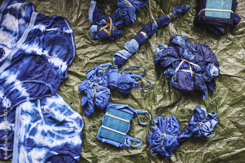 a group of clothes being tie dyed. Poster