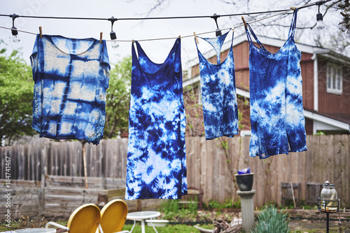 tie dyed clothes hanging on a clothes line. Poster