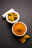 Turmeric powder in ceramic bowl with raw dried turmeric over plain background   - 184741859