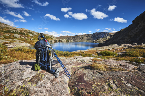 A backpack with hiking poles at a mountain lake
