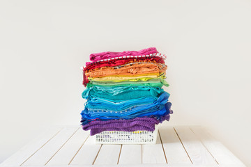 The washed laundry is in the basket. Bright rainbow clothing is stacked.