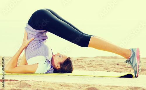 Plakat Woman practising yoga poses standing on beach