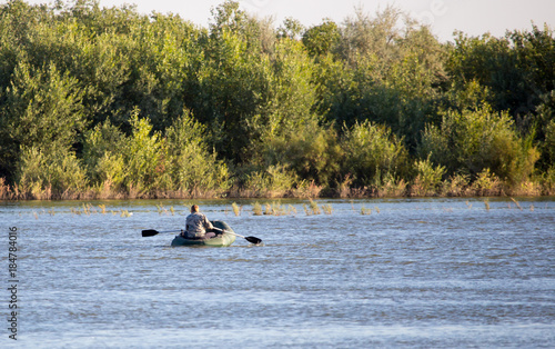 Foto Murales Fishermen in a boat sailing along the river