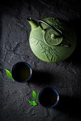 Closeup of green tea with teapot on black rock