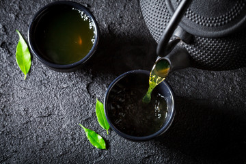 Pouring green tea into cup on black rock