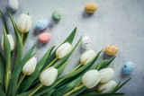 Spring and Easter background. White tulips with colorful quail eggs. Holiday concept with copy space.