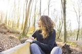 Happy girl sitting at bench - 184792670