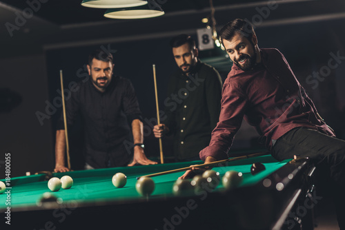company of young successful handsome men playing in  russian pool at bar