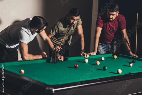 three handsome caucasian men playing in billiard at bar