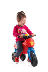 Little girl riding a motorcycle isolated on white background