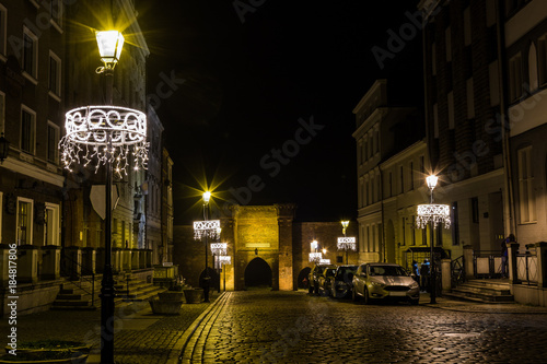 Fototapeta Nocturnal view of the Old Town cobblestone street decorated with Christams lights and Gothic Sailing Gate along the preserved fragment of defense walls. Torun, Poland on the UNESCO World Heritage Site