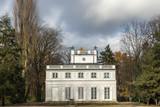Little White House built by Domenico Merlini in 1774-76 among bare trees under the dramatic cloudy sky. Royal Baths Park, Warsaw, Poland - 184820294
