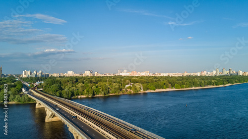 Foto op Plexiglas Kiev Aerial top view of Metro railway bridge with train and Dnieper river from above, skyline of city of Kiev, Ukraine
