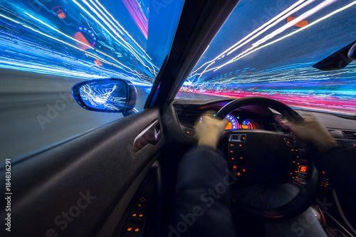 View from interrior Side of Car moving in a night city, Blured road with lights with car on high speed. Concept rapid rhythm of a modern city.