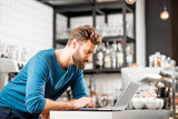 Handsome man in blue sweater working with laptop at the bar of the modern cafe interior - 184849451