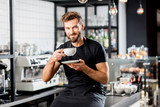 Portrait of a handsome barista sitting with coffee at the bar of the modern cafe interior - 184849818