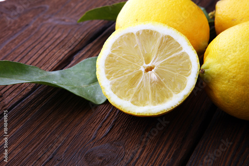 Pile of lemons with leaves on brown wooden table - 184849875