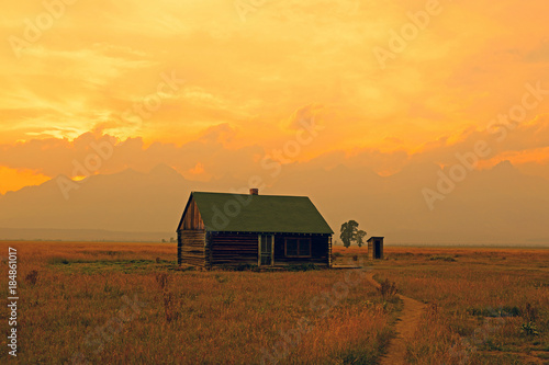 Staande foto Oranje Sunset at a historic wooden barn, Grand Teton National Park, Wyoming, USA.