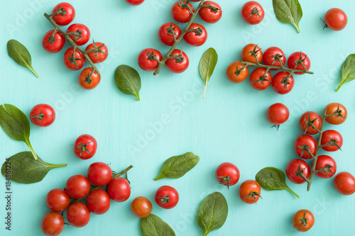Fotobehang Kersen Top view on bunches of fresh organic cherry tomatoes with small basil leaves on turquoise background. Healthy food and eating concept.