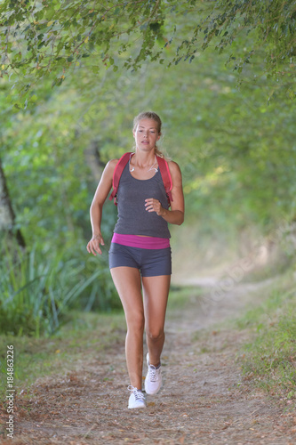 In de dag Jogging young female endurance runner jogging in the forest