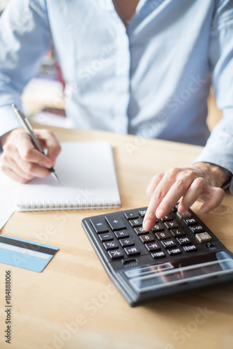 Closeup of Person Writing and Using Calculator - 184888006