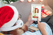 Man use tablet sending chirstms and new year gift to friend online.winter holiday at home celebration,mobile digital lifestyle,relax on sofa and listening music.