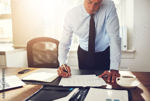 Mature executive signing contracts at his office desk