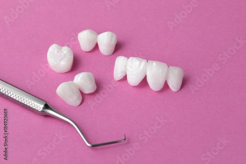 Protezy cyrkonowe z narzędziem stomatologicznym na różowym tle - okleiny ceramiczne - luminerzy