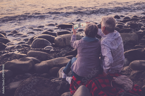 Canvas Aubergine couple of adults sitting at the beach looking at the phone and taking pictures