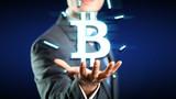 Geschäftmann mit digitalem Bitcoin Symbol über der Hand