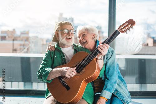 Leinwandbild Motiv Musical holiday. Waist up portrait of amorous married man and woman enjoying playing on instrument