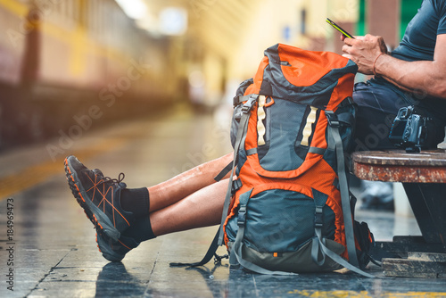 Fototapeta Tourist man with a backpack in the train station holding a smart phone. A camera on the bench. Digital nomad traveler concept