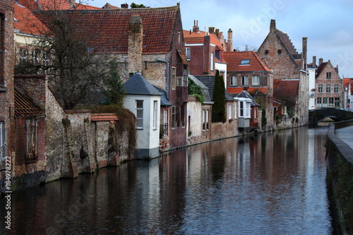 Fotobehang Brugge Old town Brugge (Bruges), Belgium. Medieval buildings exterior with tiled roofs and reflection in river canal. Brick ancient houses and walls. Medieval architecture in Europe while travel.