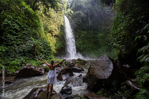 Keuken foto achterwand Bali Woman at the giant Nungnung waterfall on Bali island, Indonesia