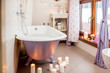 Beautiful bathroom interior with retro violet bath decorated with candles