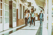 Group of mixed races teenagers group walking and smiling along school hallway