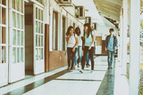 Group of mixed races teenagers group walking and smiling along school hallway - 185014259