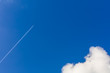 White plane flying high in the blue sky