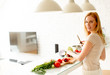 Pretty young woman preparing healthy meal in the kitchen - 185017832