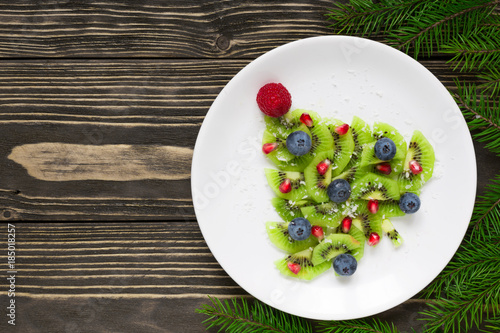 kiwi christmas tree with fir tree branches over rustic wooden table. funny food idea for kids