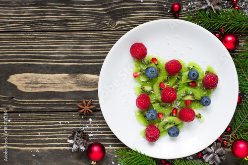 kiwi christmas tree with berries, pomegranate seeds and coconut looks like snow. funny food idea for kids