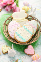 Easter cookies in basket on wooden table