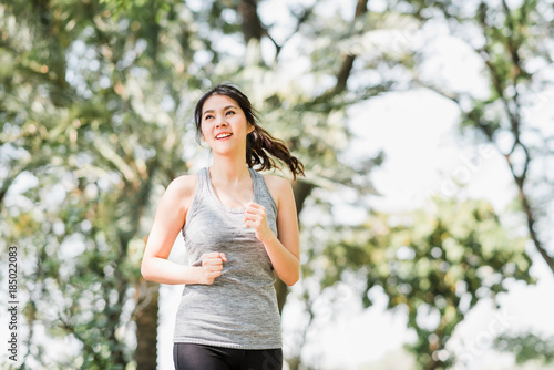 Beautiful young healthy Asian woman running in the park