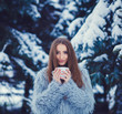 Young woman in a blue fur coat is drinking tea in the winter forest