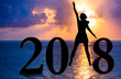 Happy new year card 2018. Silhouette of young woman on the beach stand as a part of the Number 2018 sign with sunset background