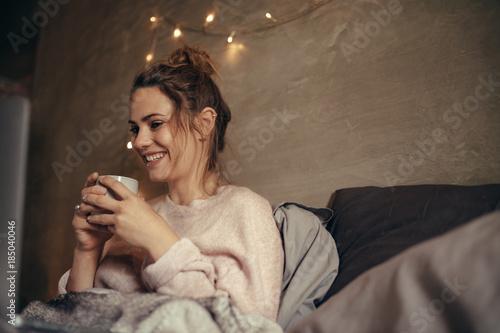 Plagát Cheerful woman drinking coffee in bedroom