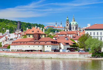 A riverside view of Vltava running through Prague with it's red rooftops on a sunny day in the Czech Republic.