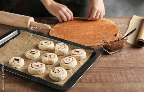 Fotobehang Kruiden 2 Baking sheet with raw cinnamon buns on table